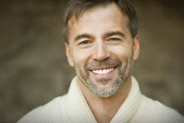 Close up portrait of man with beard smiling big after dental whitening result