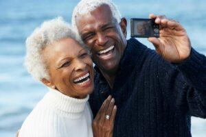 elderly dental crown patients taking photo near water