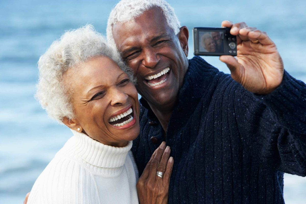 elderly dental crown patients taking photo near water