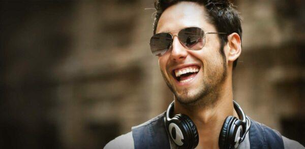Smiling man in eyeglasses during gum contouring consultation