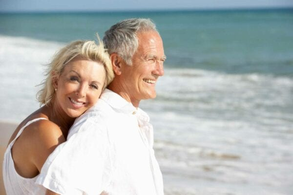 Happy couple spending time at the beach after treating tooth decay with Inlays and Onlays procedure