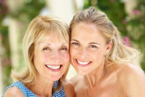 Beautiful daughter and mom showing their healthy white smile after Invisalign procedure