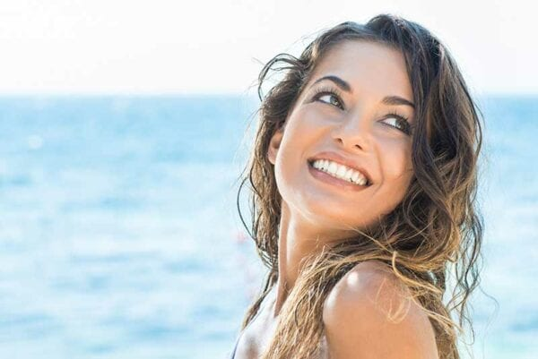 young happy woman on a beach showing off beautiful smile made by veneers