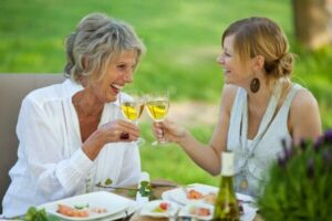 Elderly smiling woman having a glass of wine with her daughter talking about Root Canal treatment