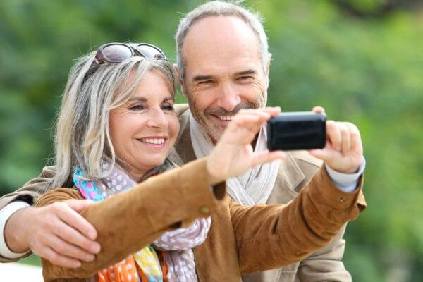 Traveling senior couple taking selfie together after dental implant consultation